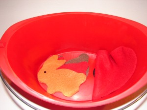 Rabbits hiding in red bucket