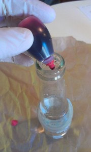 2. Place drops of food coloring in each bottle. Stir with skewer.